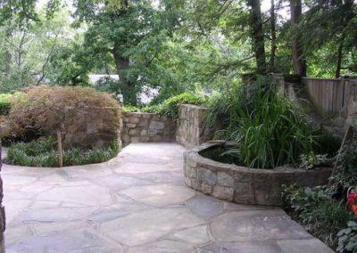 Stone backyard patio with decorative stone walls and greenery