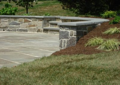 Stone retaining walls and steps in driveway