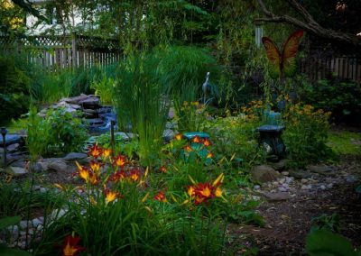 Naturally landscaped backyard with red and yellow flowers, greenery, and water feature