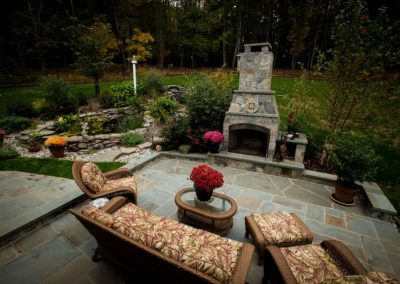 Large stone patio with seating area and fireplace in backyard