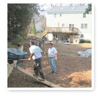 Two men working with wheelbarrow and mulch in backyard