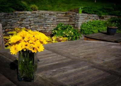 Yellow daises on wooden table in backyard near large stone decorative wall