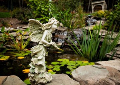 Statue of fairy in front of large pond and waterfall water feature in backyard