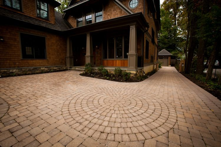 Paved driveway with pavers in a circular pattern in front of brown house