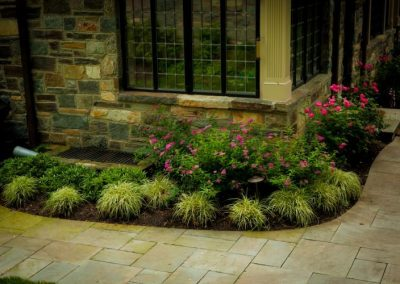 Side of house with plantings and stone pathway