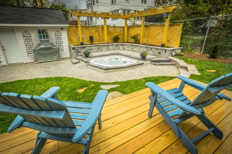 View from wooden deck with chairs overlooking hot tub in stone patio