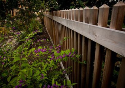 Wooden fence next to landscaped area with planters