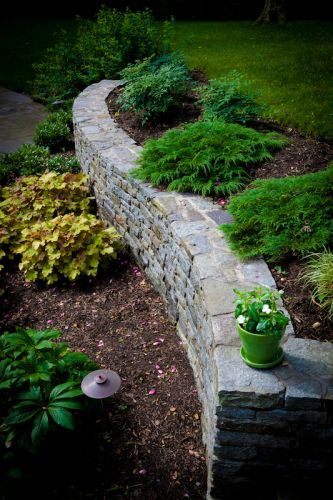 Decorative stone wall in yard with plantings
