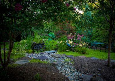 Naturally landscaped backyard with stone gravel pathway leading to water feature and greenery