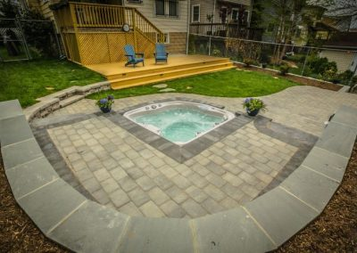Hot tub in patio in backyard with wooden deck