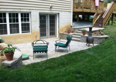 Stone paved patio with sitting area off the side of a large house
