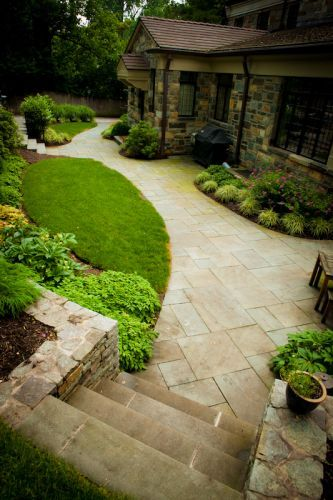 Stone patio area on side of house in landscaped lawn