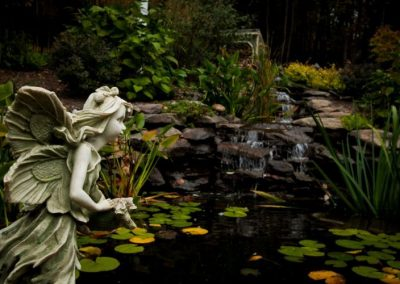 Statue of fairy in front of pond and waterfall water feature in backyard