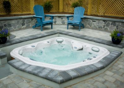 Hot tub in stone patio deck with chairs