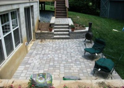 Backyard paved patio with seating area and steps