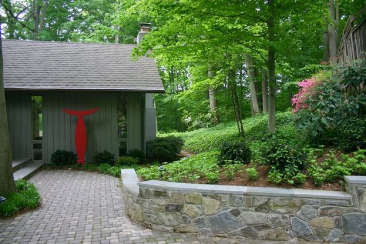 Stone retaining wall in sloped yard in front of house