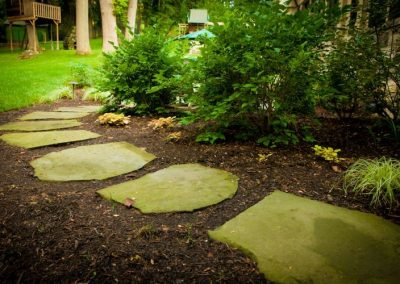 Stone pathway on mulched area leading to backyard