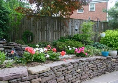 Backyard with stone retaining wall and plantings and flowers