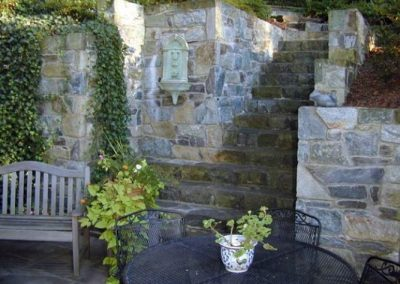 Seating area with large stone retaining wall, stone steps, and greenery