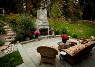 Stone patio in backyard with seating area and fireplace