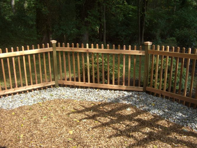 Backyard with wooden steps, mulched area, and plantings