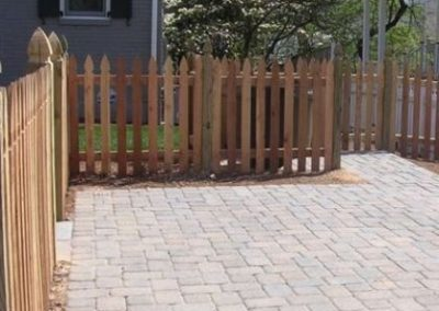 Paved driveway with wooden fence next to a house