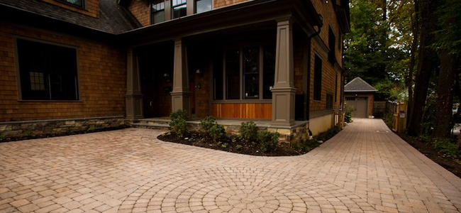 Paved driveway and side pathway in front of brown house