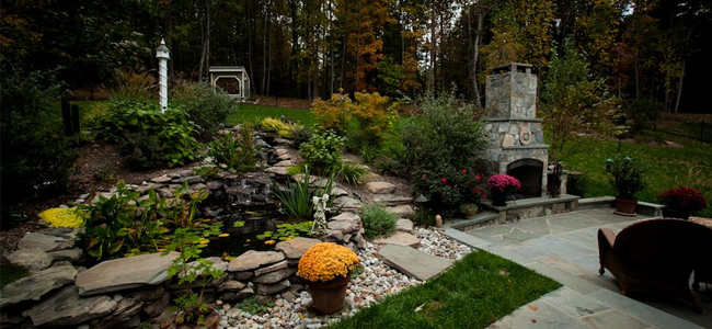 Backyard with large pond water feature, stone patio, fireplace, and steps