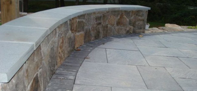 Flagstone patio next to stone wall