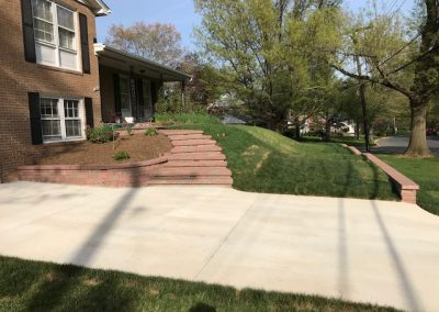 Stone retaining walls and steps in driveway.