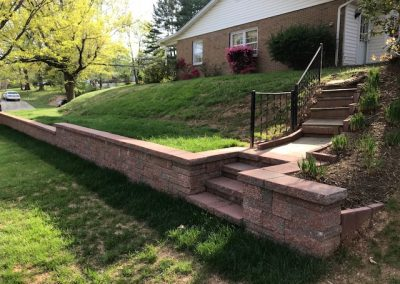Stone retaining walls and steps in front yard.