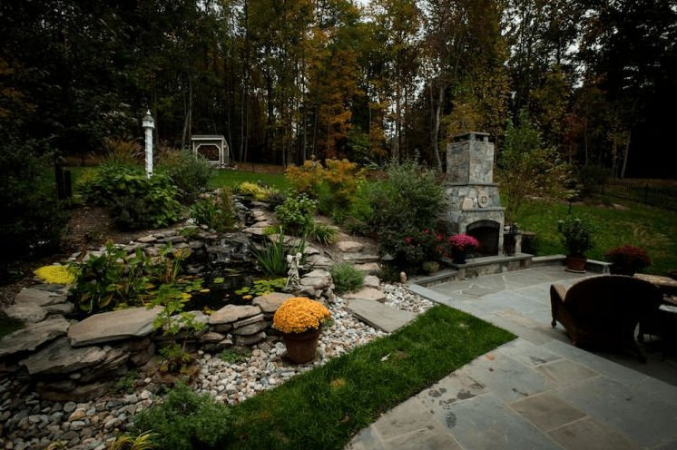 Patio with stone fireplace, pond, and grass area