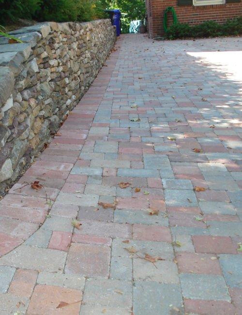 Paved driveway next to a stone wall